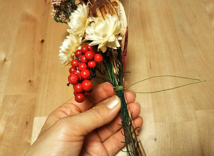 好みのドライフラワーと造花の赤い実を束ね、ワイヤーでしっかり固定します。