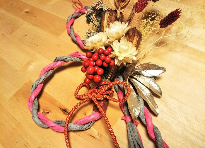 束ねた茎の部分を色付きの不織布(和紙なども可)で巻き、茎の切り口を覆って美しく仕上げます。不織布の端が後ろ側になるようにしてグルーで接着します。不織布の上から和風の紐飾りを結びます。最後に右側に金色の飾りを差し込んでプラスし、グルーで接着します。
