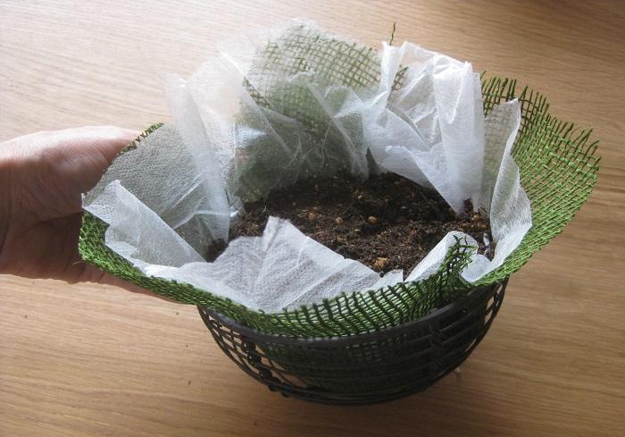 植え方を紹介します。  今回はアイアン製の器を使うので、土がこぼれ出ないように器の上に麻布と不織布を敷き、草花用培養土を入れて植えていきます。