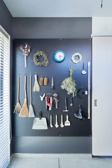 壁一面に取り付けた有孔ボード。電動ドリルやハケ、掃除道具などDIYに必要なアイテムがかけられています。ドライフラワーやリースを飾って、華やかさをプラス。