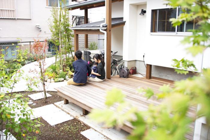 DATA 東京都 戸建て K邸 【施工内容】シンボルツリー植栽、花壇植栽、目隠しフェンス、石平板張り、砂利敷き 【広さ】 約33㎡ 【エリア】主庭、住宅外周部 【家族構成】ご夫婦+お子様2人 ご家族でお庭の話をすることも増えたとのこと。毎日生長して変化する植物を見るのが楽しみで、早起きして水やりをするようになったそうです。「これからテラスでのランチなども楽しめたらよいなと思っています。ハーブもたくさんあるので、それを料理に使うのも楽しみです」と奥様。外に出る機会が増え、お庭が生活の一部となり豊かな暮らしにつながっています。 リビング正面のお庭は正方形の石を敷き整ったクールな雰囲気に。他エリアの樹木や石のナチュラルなお庭と変化を付けています。異なる雰囲気のエリアを設けることでお庭全体のバランスを整えています。春になるとグランドカバーのディコンドラ(ダイカンドラ)が繁茂し、一面緑のお庭になるのを楽しみにされていました。