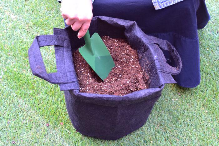 次に培養土を入れていきます。今回使用した瀬戸ヶ原花苑さんの「花と野菜のプレミアム培養土」は軽くて扱いやすいふわふわの土。元肥入りで肥料効果が約3ヵ月続くので、植え付け時の肥料が不要です。