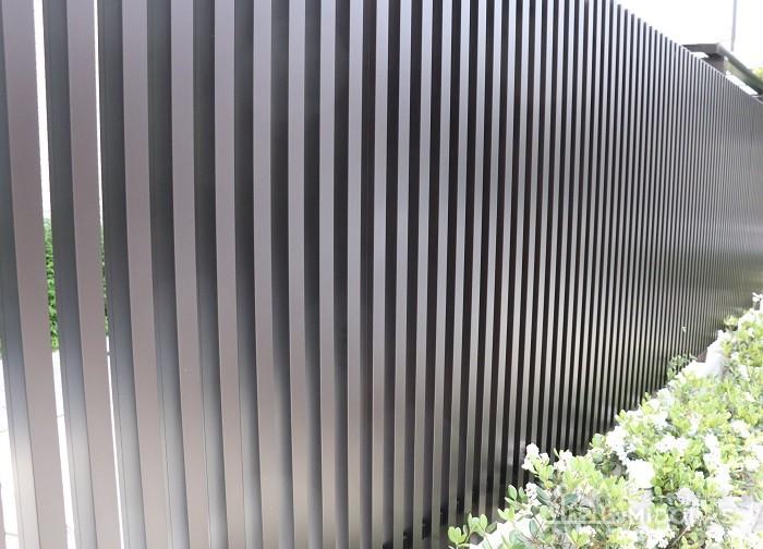 駐車場の目隠しには好みによって横ばりのフェンスや縦格子ルーバー、樹木などが使われます。