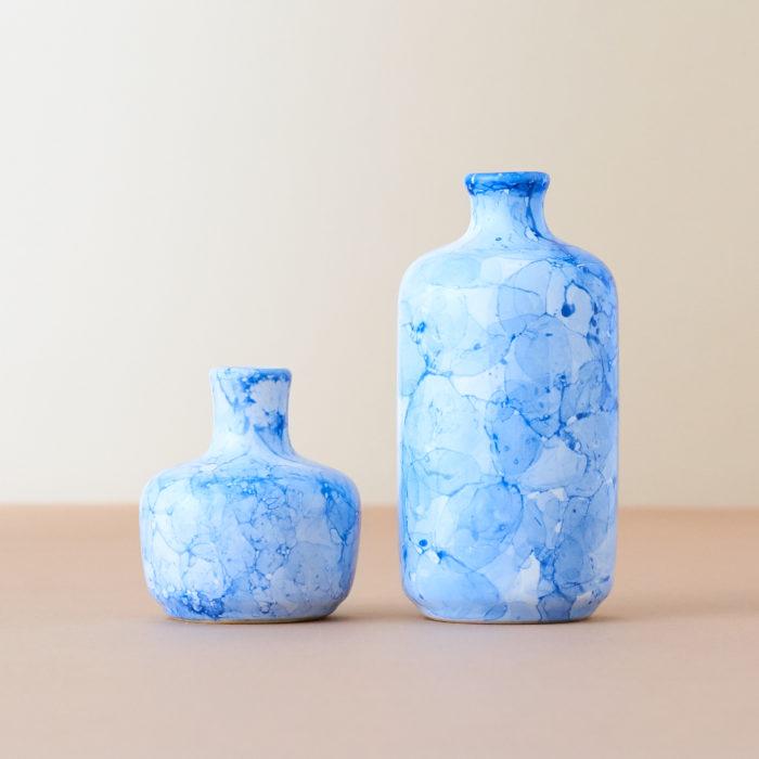 水彩のようなアートな模様が美しい花瓶。大きさが異なる2つの花瓶がセットになっています。  別々の場所に置いて飾るも良し。同じ場所に2つの花瓶を並べて飾るも良し。花瓶が統一されることでインテリア性もさらにアップします。  毎日切り戻して短くなった花もサッと飾れる便利なサイズ。生花はもちろん、ドライフラワーにもぴったりです。  夏らしい爽やかなブルーと、シックなグレーがあります。