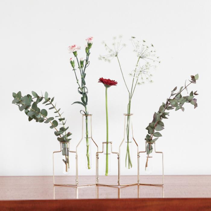"""花瓶のシルエットをかたどったワイヤーに、試験管のような細長いガラスベース。飾った花はさらに魅力を放ち、インテリアとしても馴染みやすくお部屋のアクセントに。  連結部分は動かすことができるので、花瓶自体の形も置く場所によって変えることができます。ガラス部分は取り外せるので、生花を飾るときの水替えも簡単。  カラーは華美すぎない色味が美しい """"GOLD""""と、ヴィンテージ感のある風合いの""""MAT""""2種類、サイズは3連タイプと5連タイプがあります。  色も形も、あなたの暮らしに合わせてコーディネートできるのでおすすめの一輪挿しです。"""