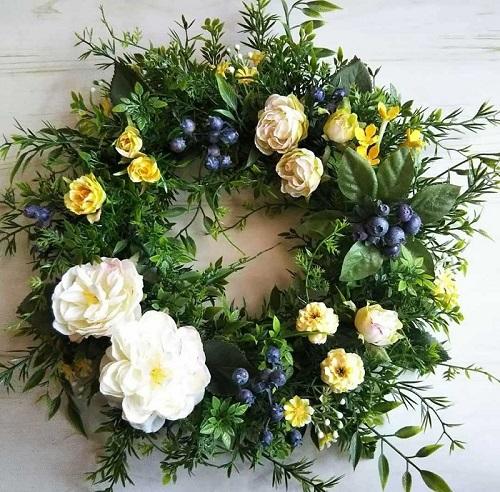 深いグリーンのリーフ類がもともと装飾されているリース台に、バラ、ミニバラ、ブルーベリー、小花などをワイヤーとグルーでつけました。簡単なのにボリュームたっぷりで見栄えするリースです。
