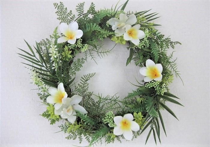 このリースは少しシャープなイメージのハワイアンリース。ワイルドなヤシの葉をアクセントに、プルメリアとシンビジウム、小花とシダなどの葉をちりばめました。
