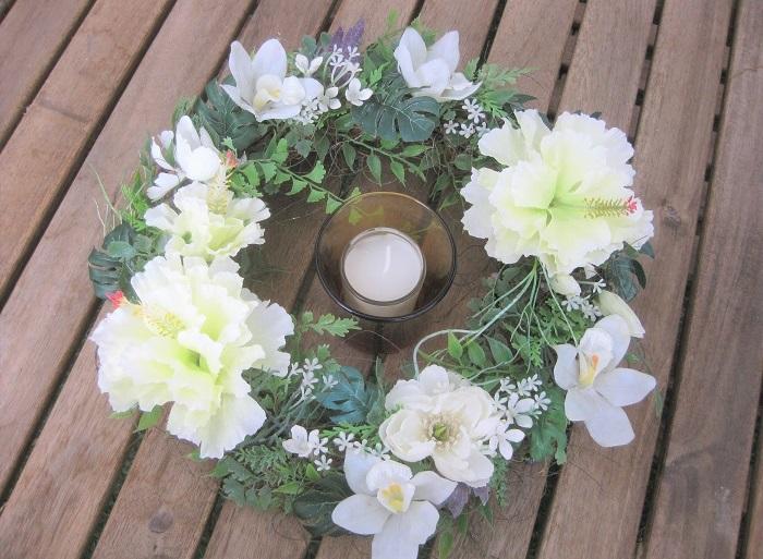 カラフルよりも白い花がお好みの方には、白とグリーンだけつくるハワイアンリースがおすすめ。白いハイビスカスとシンビジウム、モンステラやシダの葉などを使っています。このようにリースをテーブルに置き、真ん中にキャンドルを飾っても素敵ですね。