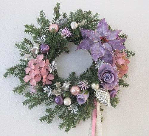 このリースは、モミの枝葉が装飾されているリース台に、ラメ付きのバラ、ポインセチア、アジサイ、ヒイラギ、キラキラパーツ、リボンを合わせています。