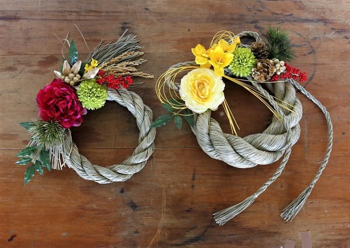 お正月には、しめ縄の土台にアーティフィシャルフラワー(造花)を合わせると手軽にしめ縄飾りが作れます。牡丹、芍薬、ダリアなどのメインの花に、マム、松、松ぼっくり、実もの、金色のパーツなどを付けて飾りつけしました。