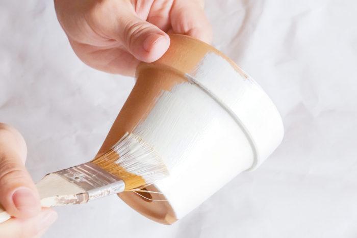 2.ハケで全体に塗料を塗ります。鉢の底の部分をペイントする時は、手を鉢の内側に持ち替えて塗ります。