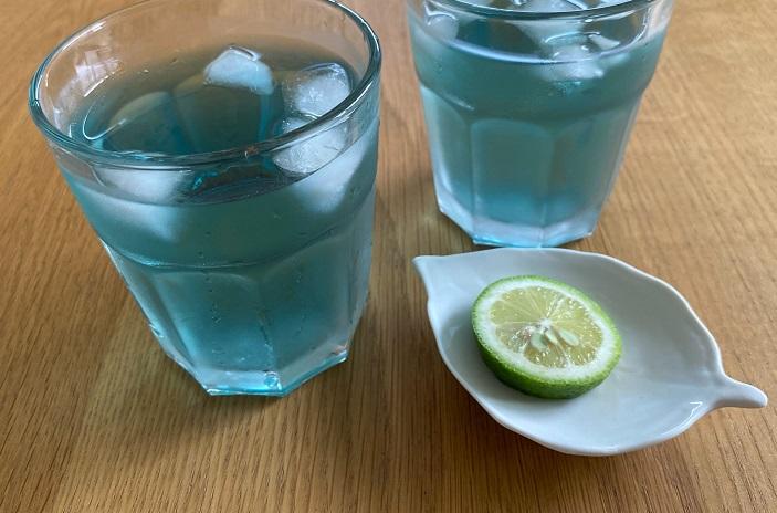 バタフライピーの花の青には、アントシアニンという天然の青い色素が含まれています。出来上がったお茶にレモンなどの酸性のものを垂らすと、アントシアニンがレモンのクエン酸と反応して、青から紫色に変化する性質があります。  それでは実際に今回はライムをしぼり入れてみます!
