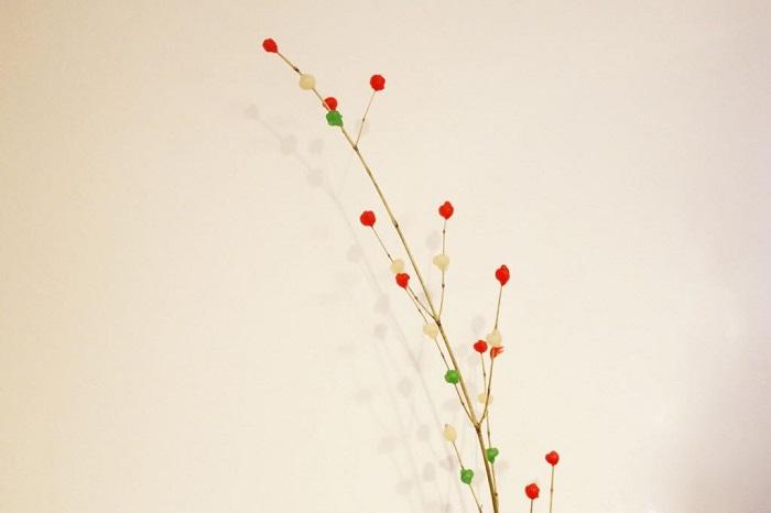 小正月に飾る花、餅花。  餅花とはお正月の花材として木の枝に紅白の餅や団子を付けて作る、新しい一年の五穀豊穣を願って作る縁起ものです。餅花についた餅を小正月が終わった後に焼いて食べると、その年一年、無病息災でいられるとの言い伝えもあるそうです。