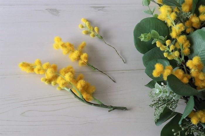 グリーンがあらかじめ付いているリース台には、ミモザのアーティフィシャルフラワー(造花)をサイズ違いに小さく分けてワイヤリングしてランダムにさします。