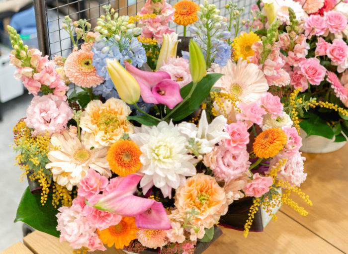 トルコギキョウ、ガーベラ、キンギョソウ、ミモザ、ユリ、カラー、バラ、ストック、ダリア、デルフィニウム、カンパニュラ、ビバーナムなど、たくさんのお花がつかわれたフラワーアレンジメント