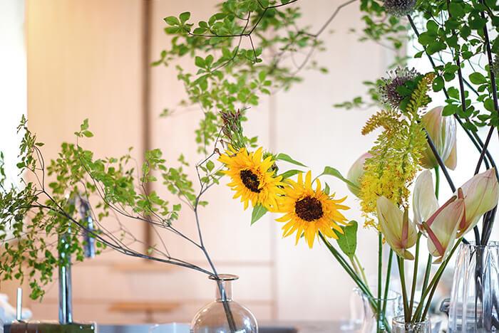 ひまわりを飾りながら涼やかさを出したい時には、ドウダンツツジなどのグリーンの枝物と合わせるがオススメです。キッチンやリビングに飾ると部屋の雰囲気がぱっと明るくなります。一緒に飾る花もグリーン、イエロー、ベージュ系でまとめるとより統一感がでます。