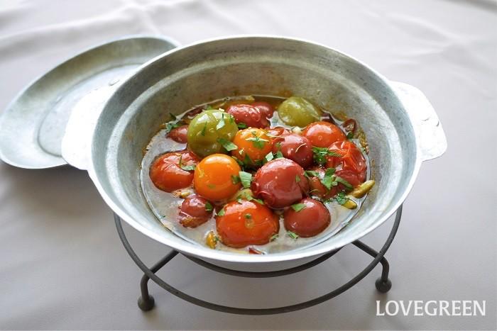 カラフルミニトマトのオイル煮 ミニトマトだけ。お肉もブイヨンも使ってないのに、びっくりするほど味の濃い一皿です。パスタに和えてもおいしくいただけます(その際は少し塩分を強くしてください)  材料 カラフルミニトマト(ミニトマトでも可)食べたいだけ ニンニク1~2片 鷹の爪1本 塩少々 オリーブオイル適宜 作り方 ミニトマトを洗って水気を切っておく ニンニクは芯を取ってスライス 鷹の爪は種を取って輪切り 小鍋にミニトマト、ニンニク、鷹の爪を入れ、オリーブオイルを回しかけ蓋をして弱火で煮込む(落し蓋のような物が望ましい。なければ上からアルミホイルで覆っても可) 途中蓋を開けて、中のミニトマトにシワが寄り、水分が出てきていたら塩を少々振って、また蓋をする 5分くらい経って、十分にミニトマトがしんなりしていたら出来上がり